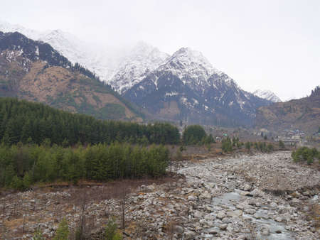 Dried up portion of the Beas River in winter, with snow-capped mountains in the background in Manali, Himachal Pradesh India. Banco de Imagens