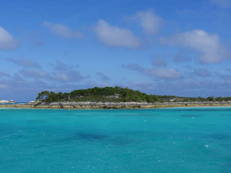 Rocky island covered in greens dotting the vast blue ocean of Bahamas in the Exuma Cays.