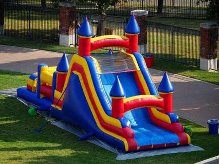 Colorful bouncy castle sitting on a grassy park Stockfoto