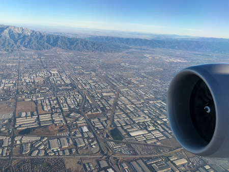 Medium wide aerial view of the outskirts of Los Angeles, California with the tip of a jet engine in view.