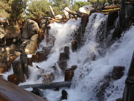 Artificial waterfalls with wood pieces to control the flow of water in a park