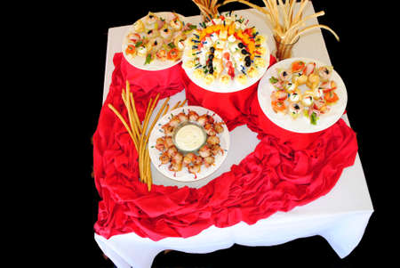 Different appetizers in plates with a heart-shaped table cloth, dark background