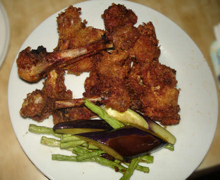 Crispy breaded chicken drumsticks served with eggplants and green beans Banco de Imagens