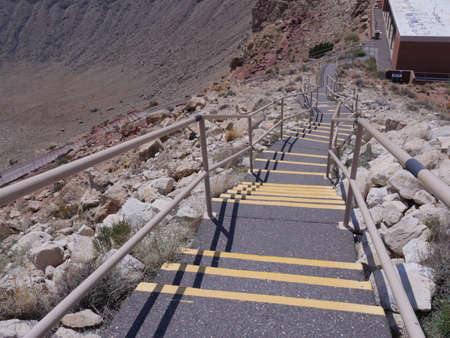 Downward view of the concrete stairs with railings at the rim of Meteor Crater, formerly known as Canyon Diablo Crater in Arizona. 스톡 콘텐츠