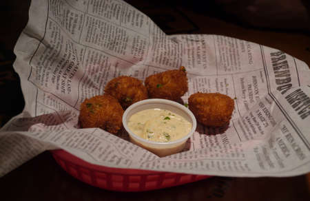 Tray of hush puppies and tartar sauce for dipping on a newspaper page Banco de Imagens