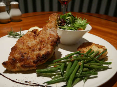 Close up of a roasted half chicken portion with green beans and vegetable salad