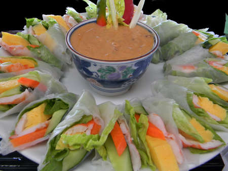 Tastefully arranged fresh vegetable lumpia with a bowl of sauce for dipping