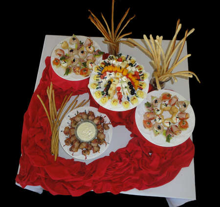 Wide shot of an assortment of hors d'oeuvres in plates with a heart-shaped table cloth