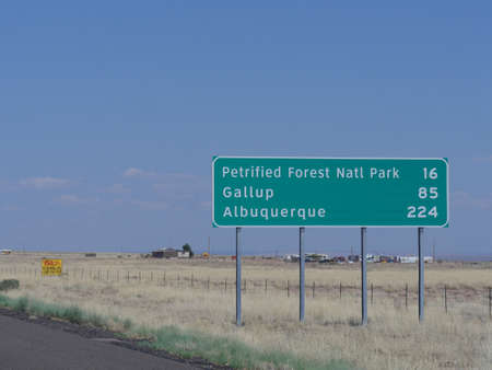 Directional sign on the road in Arizona with distance information to the Petrified Forest National Park, Gallup and Albuquerque.