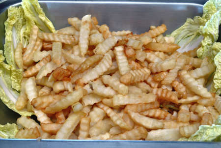 Tray of french fries on a bed of vegetables Banco de Imagens