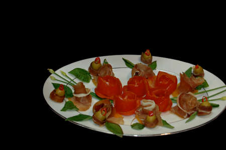 Plate of fresh red tomatoes and rolled bacon appetizers