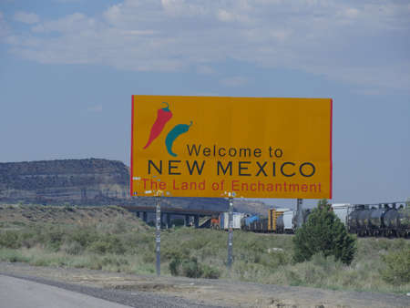 Medium wide shot of the Welcome sign at the state border of New Mexico and Arizona, USA.