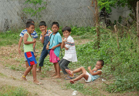 DAVAO ORIENTAL, PHILIPPINES—MARCH 2016: A group of happy boys posting for the camera at the side of the road in Davao Oriental, southern Philippines.