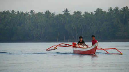 DAVAO ORIENTAL, PHILIPPINES—MARCH 2016: Two boys on a red and white boat fishing in the lagoon of Puntalinao, Davao Oriental, southern Philippines.
