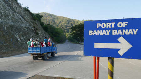 DAVAO ORIENTAL, PHILIPPINES—MARCH 2016: A blue pick up full of passengers travel along the paved road of Banay Banay, Davao Oriental, southern Philippines. 報道画像