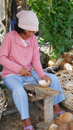 DAVAO ORIENTAL, PHILIPPINES—MARCH 2016: A woman shells coconut meat with a sharp knife outdoors while sitting on a wooden bench.