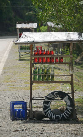 DAVAO ORIENTAL, PHILIPPINES—MARCH 2016: Gasoline sold in empty soda bottles and sold in the roadsides is a common thing to see along the highway in Davao Oriental. 報道画像