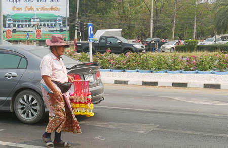 THAILAND—A woman sells flower leis to vehicles at a traffic light in one of the roads to the northern part of Thailand. Photo taken in March 2016. 報道画像