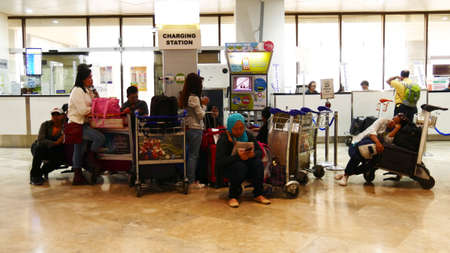 MANILA, PHILIPPINES—MARCH 2016: Passengers charging their phones and gadgets while waiting for their departure flights at the Ninoy Aquino International Airport 2 in Pasay, Manila, Philippines.