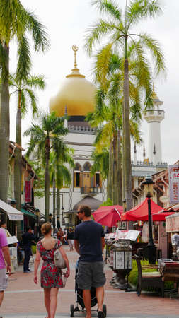 SINGAPORE—MARCH 2016: Tourists walking along the streets with colorful shops at the Muslim Quarter in Kampong Glam, a popular tourist destination in the country.