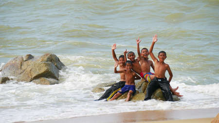 NARATHIWAT, THAILAND—MARCH 2016:  Boys sitting on a stone and waving while playing at a beach in Narathiwat, southernmost part of Thailand near the Malaysian border.