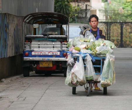 BANGKOK, THAILAND—MARCH 2016:  A young man sells fresh vegetables and fruits from a push cart along the streets of Bangkok, Thailand.