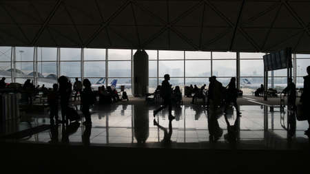 Silhouette of passengers waiting for their flights at the Beijing International Airport late one afternoon.