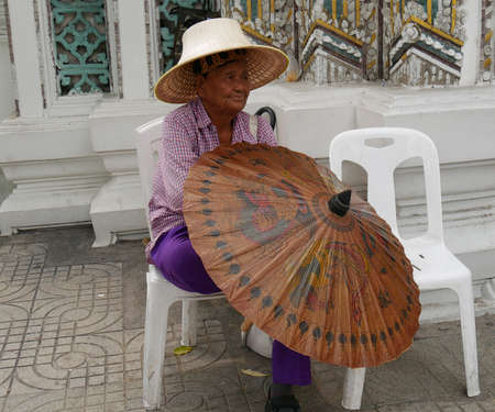 BANGKOK, THAILAND—MARCH 2016: An elderly woman sits on a chair with a ready umbrella for rent to tourists who visit the Wat Pho temple in Bangkok, Thailand. 報道画像