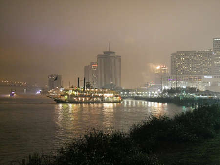 NEW ORLEANS, LOUISIANA—A dinner cruise boat at the Mississippi River heads to dock on a cold foggy night in January 2017.