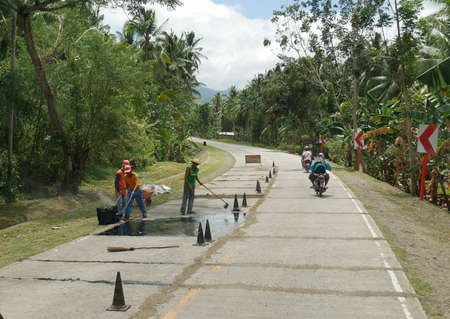DAVAO ORIENTAL, PHILIPPINES—MARCH 2016: Road workers doing repairs at the national highway to Davao Oriental, southern Philippines on a bright day.