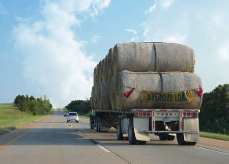 MOBILE, ALABAMA—A truck carrying an oversize load of hay bales travelling along the interstate in Mobile, Alabama in September 2015. 報道画像
