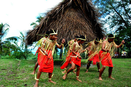 CNMI-USA—CIRCA MARCH 2011: A group of barefoot male cultural dancers entertain a cultural show opening wearing red skits and coconut leaves around their bodies, heads and feet.