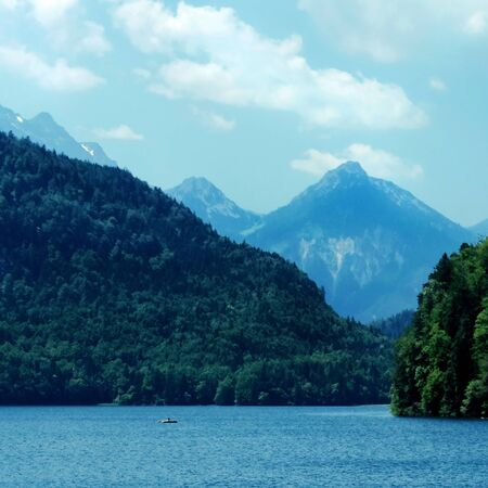 Alpsee lake landscape with Alps mountains near Munich in Bavaria, Germany. Crystal clear mountain lake and rocky mountains 写真素材