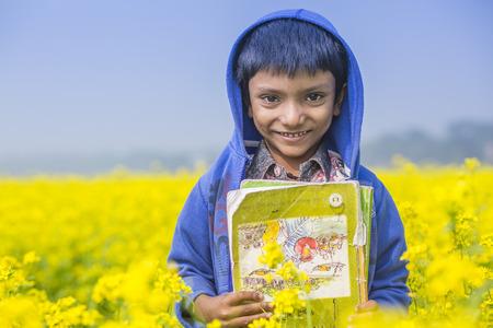 mustard field: A school kid smiling in the mustard field.