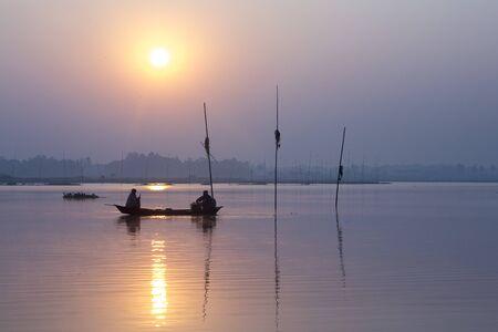 Sunrise time fisherman fishing in Kaliganga River, Dhaka, Bangladesh.