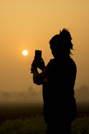 Silhouette of Asian girl photography and selfie with mustard flowers field at sunrise time.