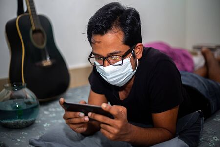 A surgical mask-wearing young man was playing mobile games on his own home due to coronavirus home-quarantine at Dhaka.