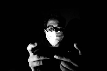 Portrait of a young man playing Mobile video games at Night deu to coronavirus epidemic.