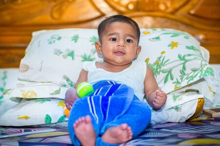 A asian baby boy is looking and playing at colorful toys.