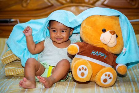 A six months age asian baby boy playing a yellow taddy bear.