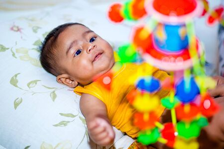 A baby boy is looking and playing at colorful toys.