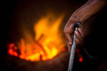 Unsafe worker hands. A local steel machine parts making yard worker melting scrap on hot furnace. Foto de archivo