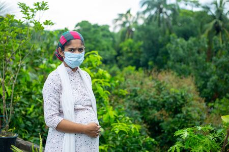 A young pregnant woman wearing a medical mask is standing in the green nature of the coronavirus epidemic. Stock Photo