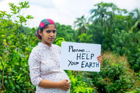 A young pregnant woman standing with a placard message to