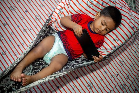 Before going to sleep a child is lying a homemade hammock and watching cartoons using a smartphone tab. Kids playing with smartphone. Mobile phone and internet addiction concept. Reklamní fotografie
