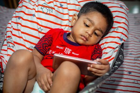 Before going to sleep a child is lying a homemade hammock and watching cartoons using a smartphone. Kids playing with smartphone. Mobile phone and internet addiction concept. Reklamní fotografie