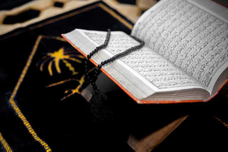 An open The holy Quran with black Tasbeeh. The Holy Quran on the mat of prayers. Focus on font and pages.