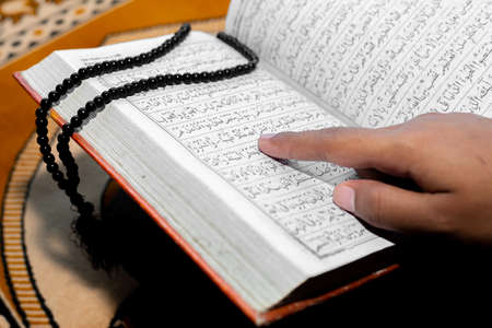 Muslim woman reading the Holy Quran using the finger. The Holy Quran on the mat of prayers . Close-up views. Indoors. Focus on hands.