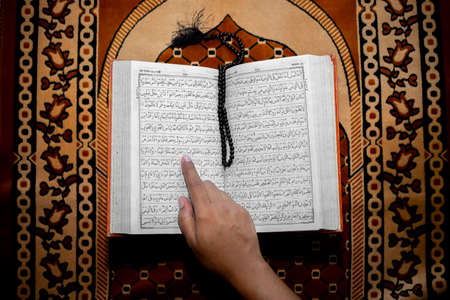 Muslim woman reading the Holy Quran using the finger. The Holy Quran on the mat of prayers . Top angle views. Indoors. Imagens