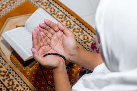Muslim Asian women raise their hands to pray on the mat at home. Indoors. Focus on hands. Imagens